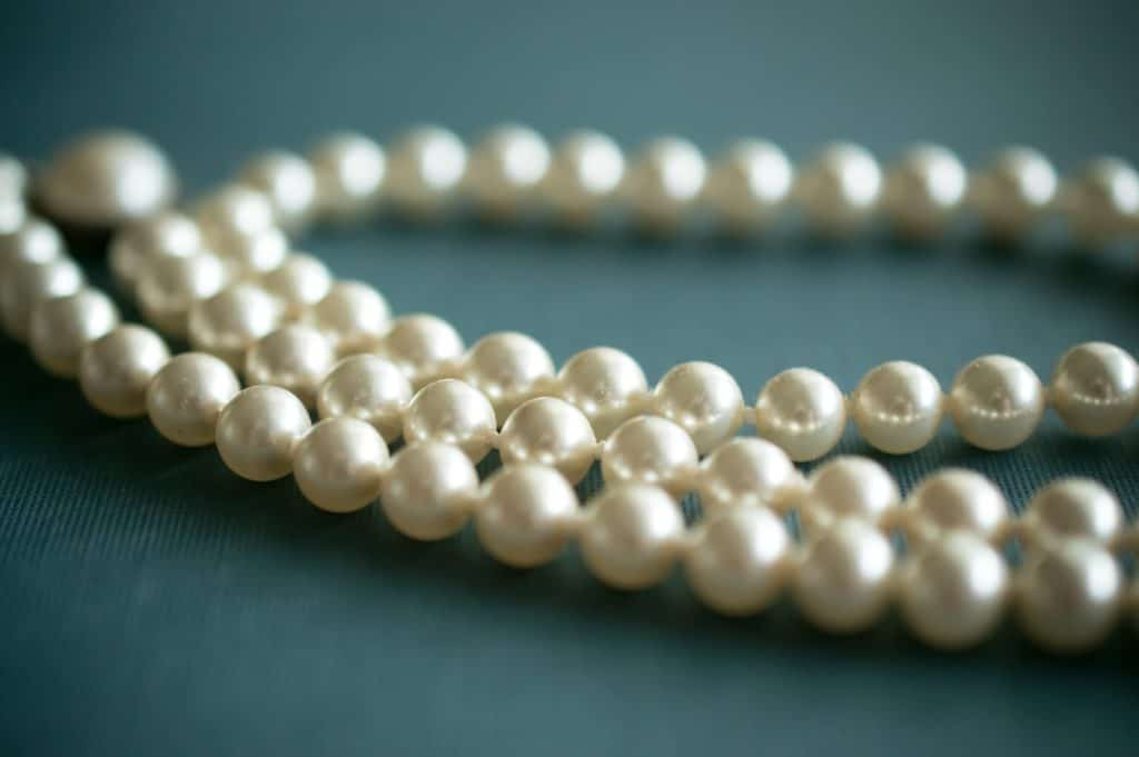 white pearl necklace on gray textile